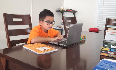 student sitting at table at home with laptop